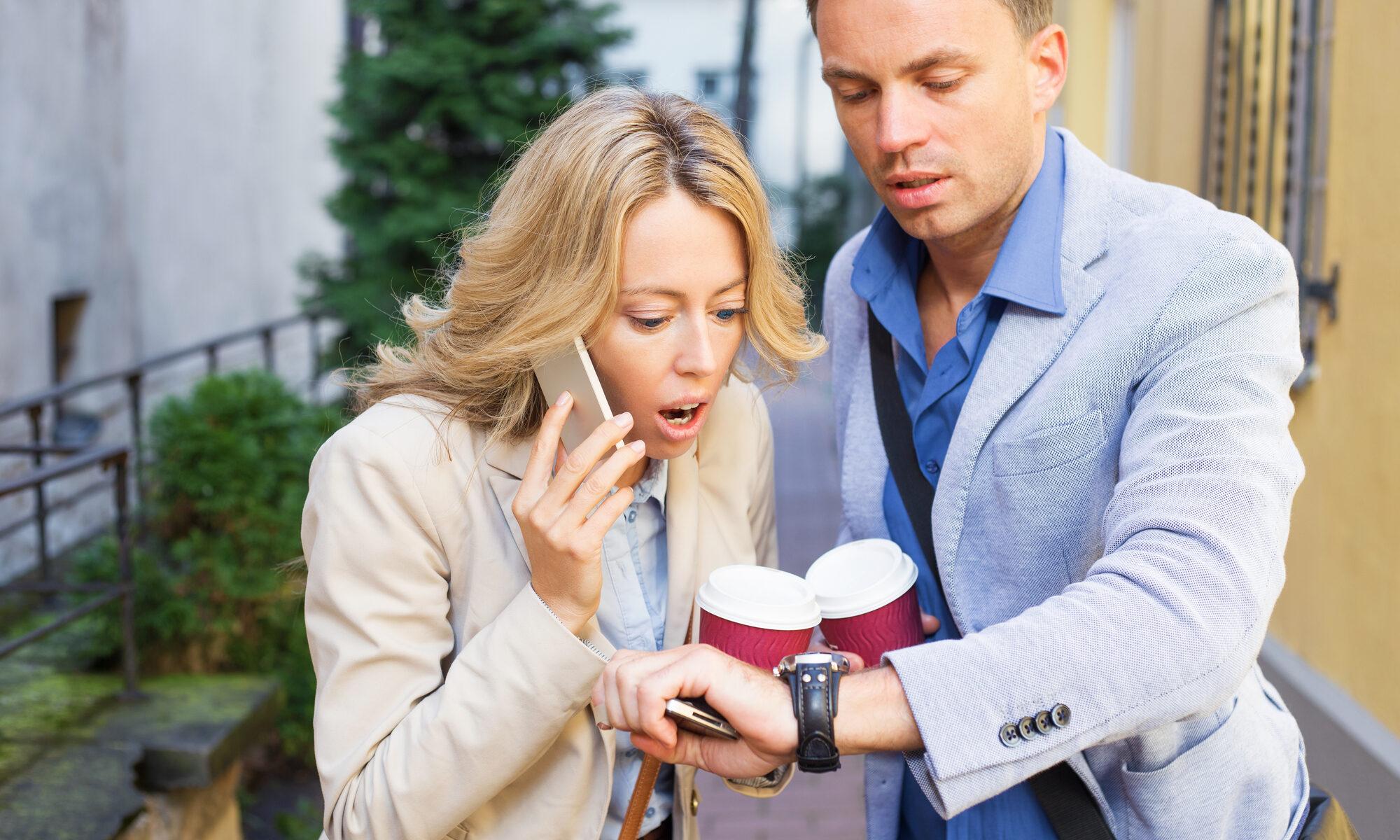 Mann und Frau gestresst mit Handy und Coffe-to-go in der Hand